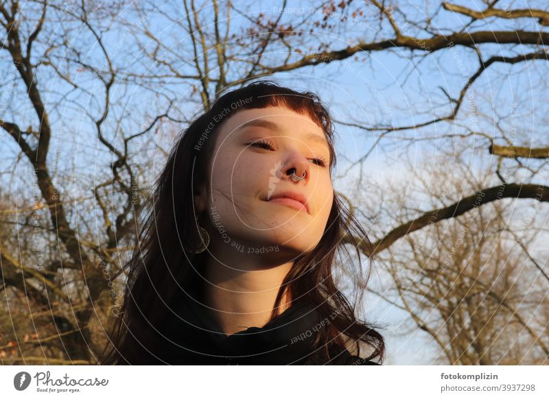 Portrait of young smiling woman under bare trees Woman Face of a woman portrait smilingly Long-haired Identity feminine Looking look optimistic Girl