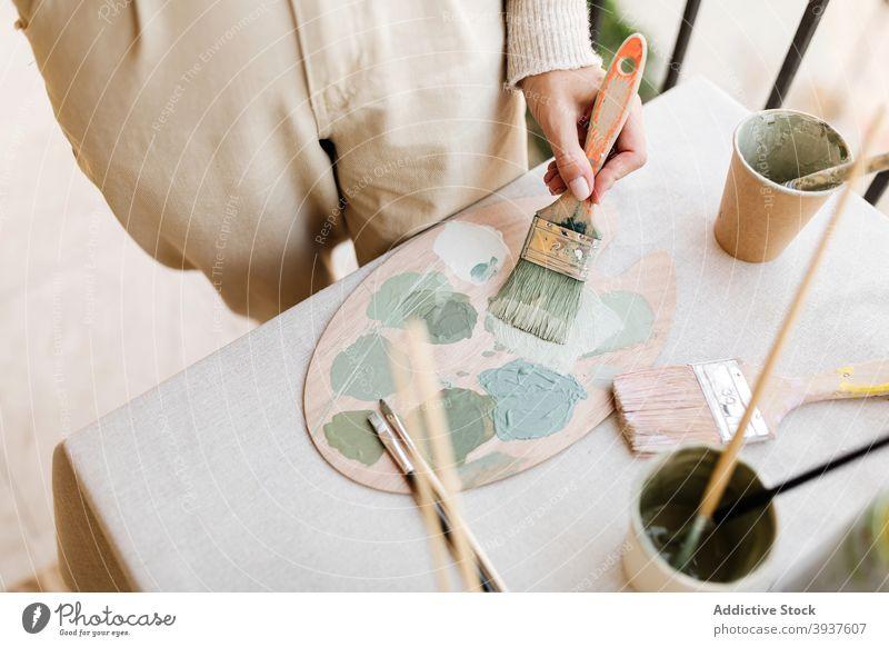 Crop female artist mixing colors on paint palette brush woman paintbrush workshop painter creative bright pastel pigment green tool talent design craft studio
