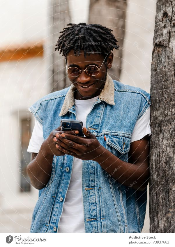 Black man using smartphone on street hipster trendy browsing style gadget afro device young positive african american black denim jeans guy dreadlocks park