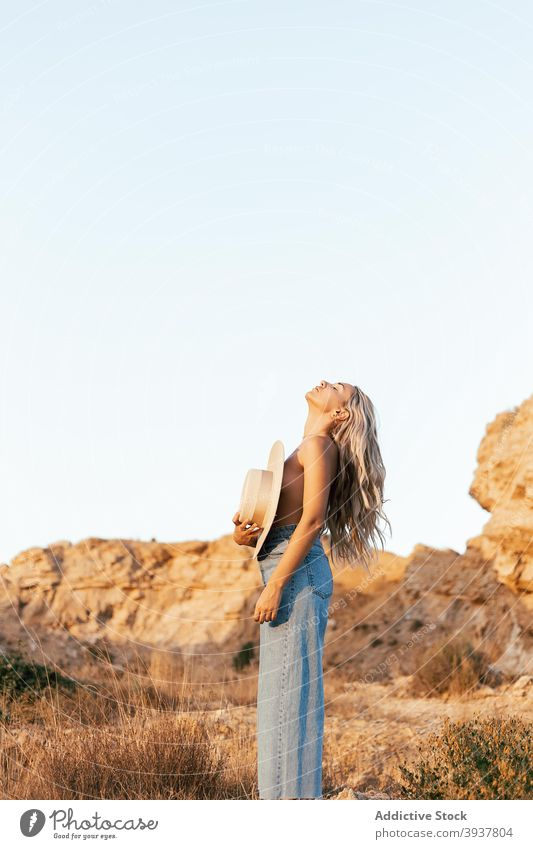 Naked woman covering breast with hat in nature slim topless tranquil enjoy sunset style female jeans relax harmony stand summer naked serene calm evening young