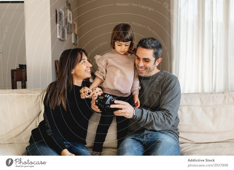 Happy family resting together on sofa at home child content mother father photo photo camera soft couch room relax living room smile casual sit happy cheerful