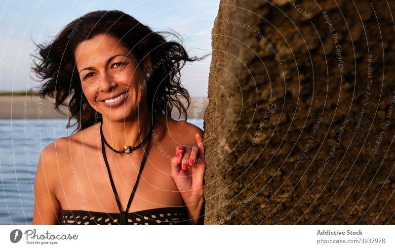 Smiling woman near rock at seaside summer beach vacancy smile enjoy cheerful sunset female algarve fuseta beach portugal vacation shore ocean bikini travel