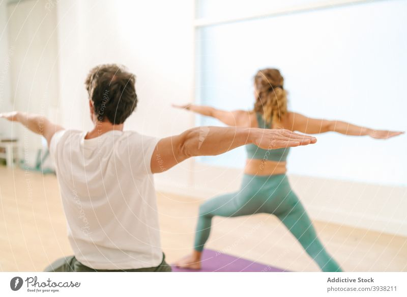 Man and woman doing yoga in Warrior pose in studio warrior pose practice balance together class zen barefoot outstretch arm flexible asana wellness