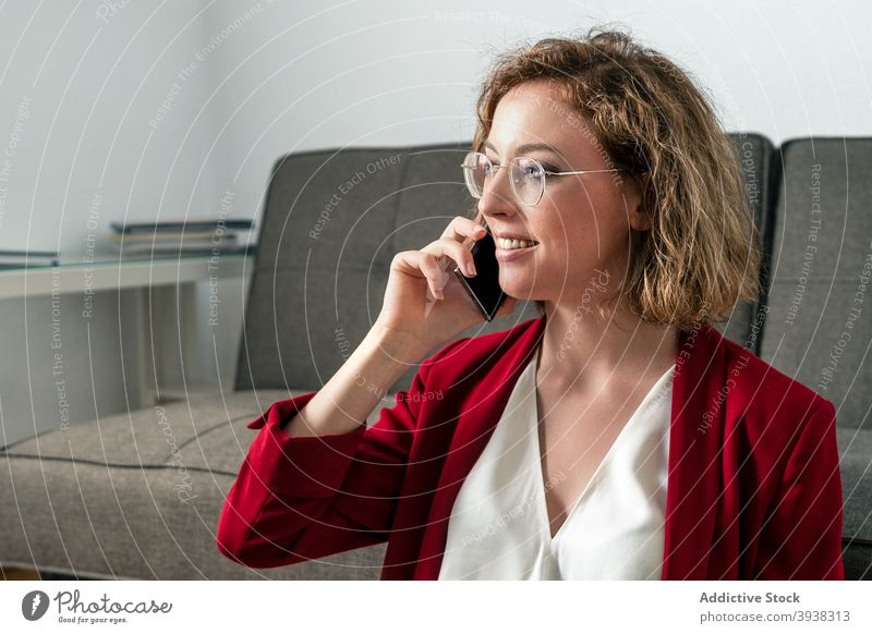 Positive young female employee discussing project on smartphone businesswoman phone call smile happy classy talk conversation communicate connection office