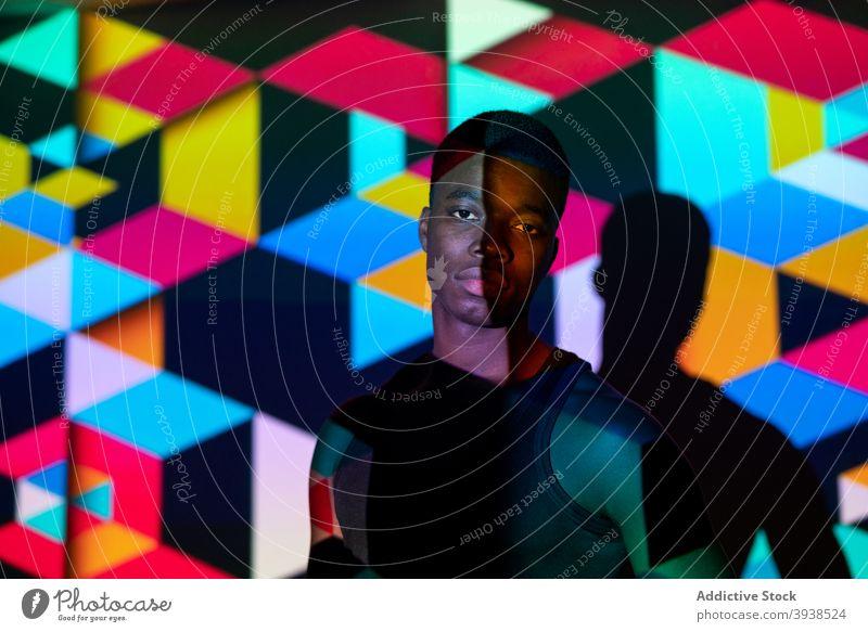 Ethnic man in dark studio with colorful neon illumination light cube geometry illuminate vivid model male black ethnic african american style trendy fashion