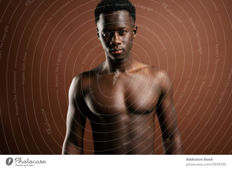 Stylish black man with naked torso in studio jeans style trendy model muscular shirtless fashion confident male ethnic african american macho masculine handsome