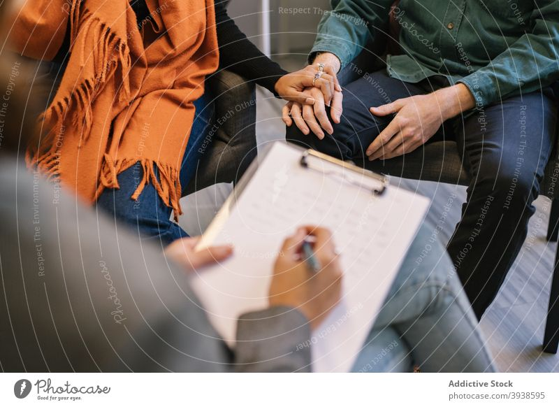 Anonymous doctor taking notes during psychotherapy session with couple woman take note relationship therapist mental support psychology patient advice help