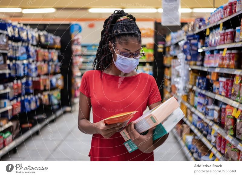Latin young woman wearing a face mask shopping in supermarket 20s latina female Covid-19 coronavirus lockdown outbreak Colombia Latin America afro black