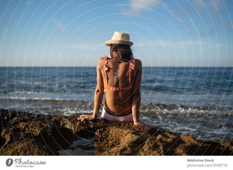 Unrecognizable female traveler enjoying sunny day on rocky seashore woman sunbath beach relax holiday resort ocean coast young swimwear straw hat suntan