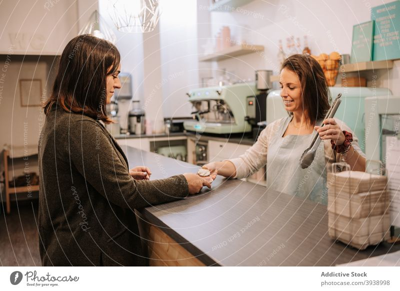 Woman buying sweets in cupcakery confectionery customer seller serve candy dessert happy women shop cheerful retail client buyer counter female positive food