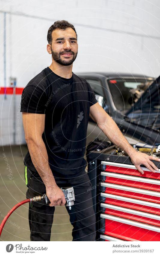 Busy mechanic with tool cabinet in car workshop man technician service instrument station male job garage maintenance repair glove handyman auto occupation