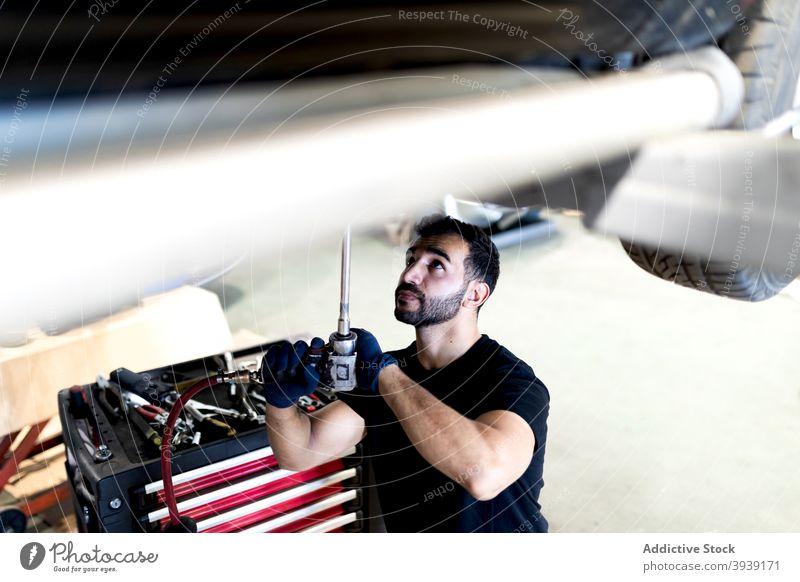 Mechanic with professional tool repairing car man mechanic service fix automobile technician instrument male transport garage maintenance metal modern repairman