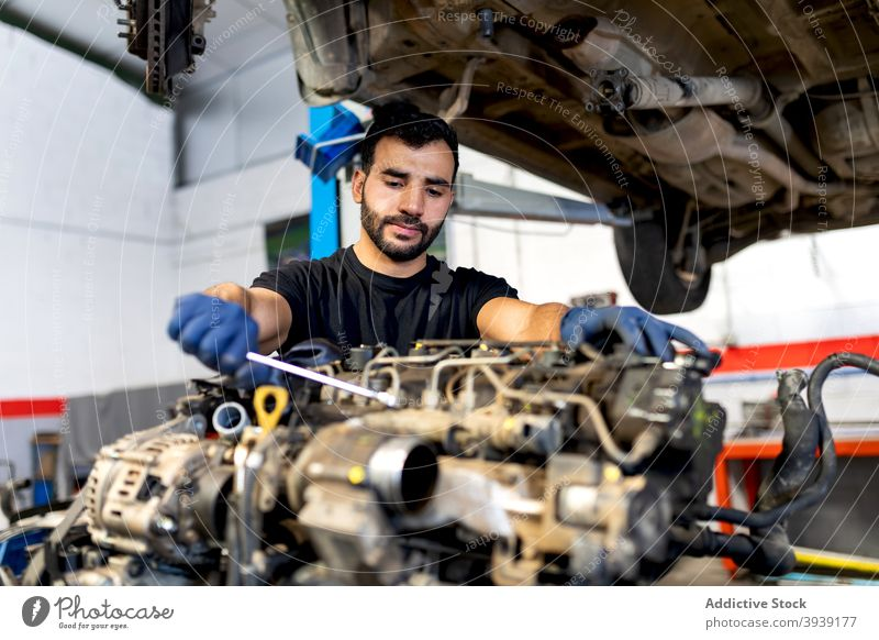 Male mechanic fixing car in workshop man engine service examine wrench spanner motor male technician professional automobile job diagnostic transport