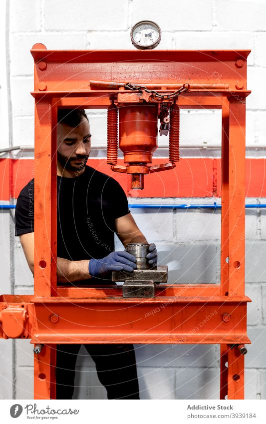 Male mechanic with car bearing in workshop man press service detail metal mechanism male technician job vehicle maintenance auto repair modern equipment guy