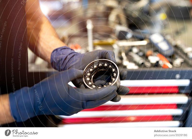 Crop male mechanic with car bearing in workshop man service detail round metal wheel technician job vehicle maintenance auto modern equipment guy professional