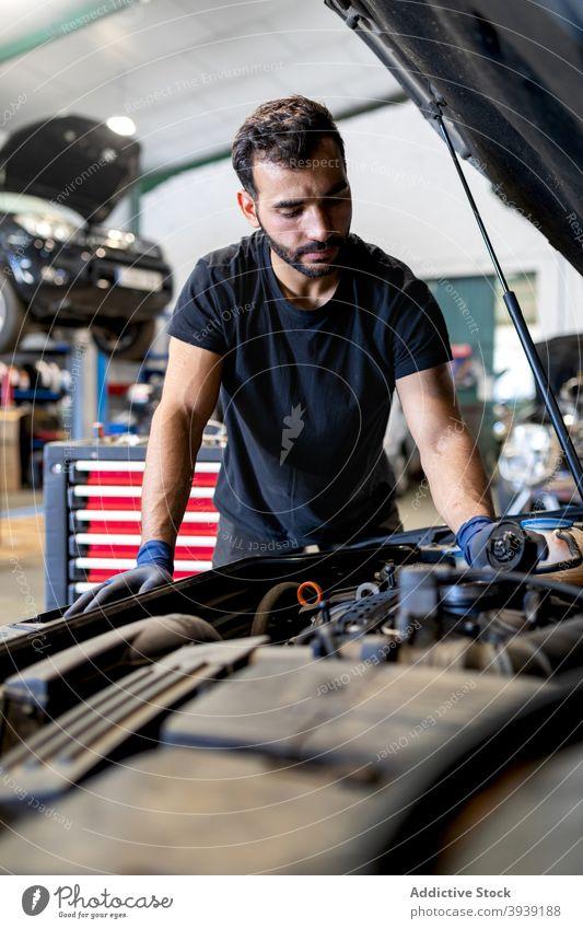 Mechanic checking car engine in workshop mechanic man oil examine inspect technician service male cap professional automobile job fix diagnostic transport