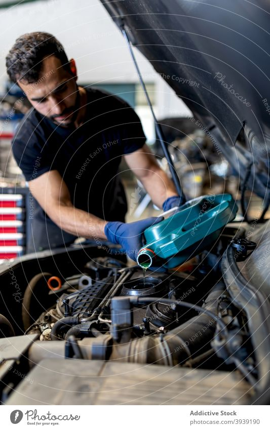 Male technician changing engine oil in car service man change motor pour maintenance male mechanic serious garage vehicle occupation job manual tool workshop