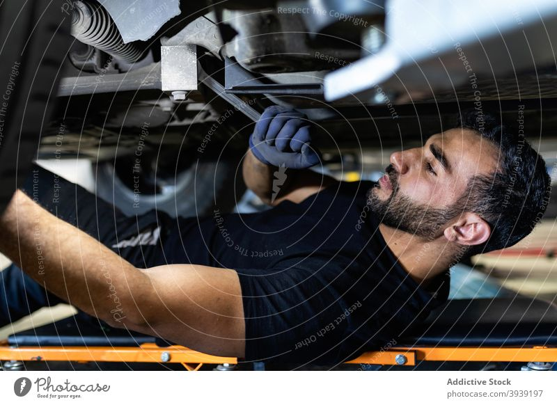 Male mechanic screwing wheel detail with wrench man car service automobile repair transport male creeper technician lying part garage maintenance fix metal