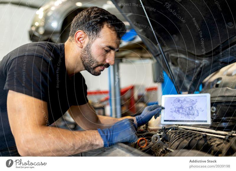 Male mechanic checking car engine in service man examine inspect technician scheme diagram male professional automobile job fix diagnostic transport maintenance
