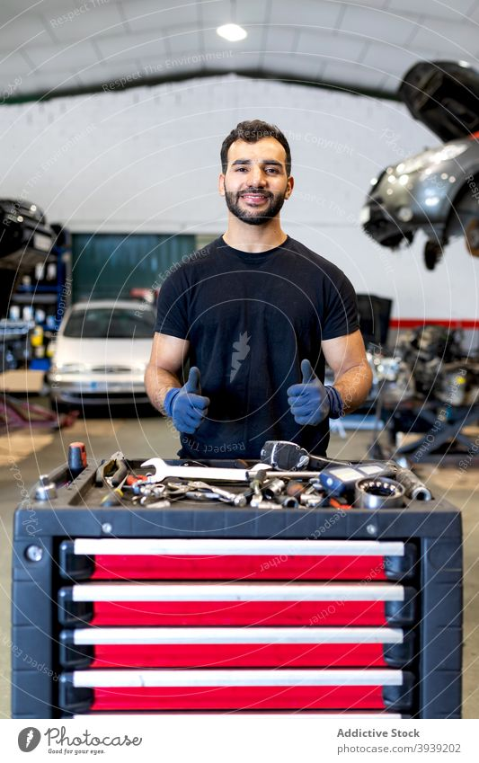 Smiling man with tool cabinet in car service mechanic technician instrument thumb up gesture male various happy job friendly garage maintenance positive work