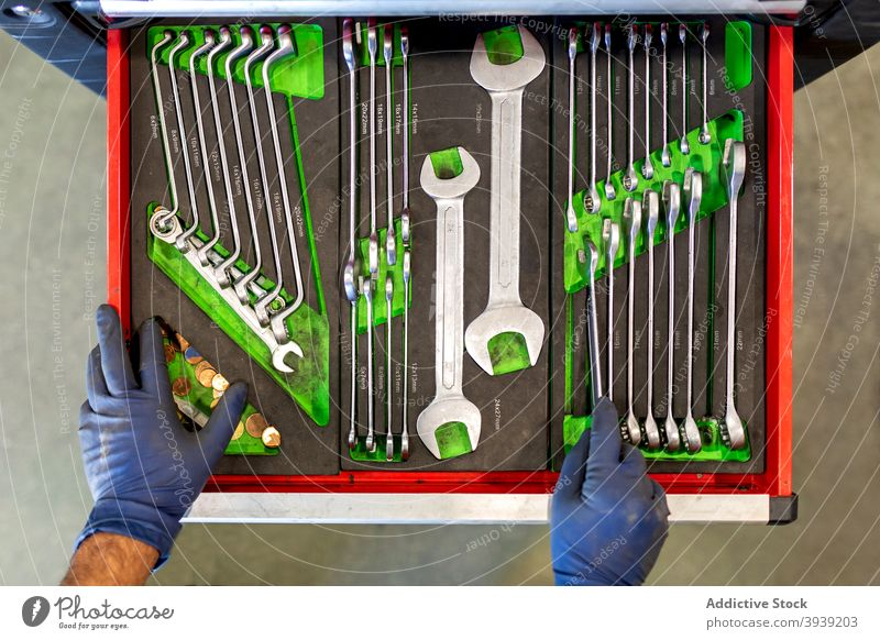 Crop mechanic with various tools in car workshop cabinet wrench man spanner key collection service male technician instrument station job garage maintenance