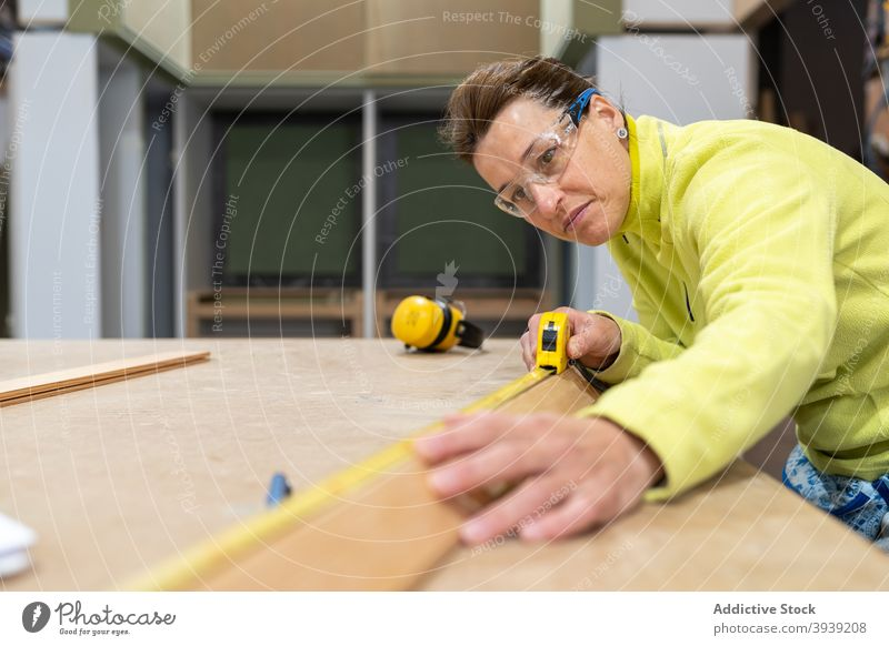 Focused young female joiner using measuring roulette in workshop woman measure woodwork concentrate joinery wooden plank carpenter professional job meter