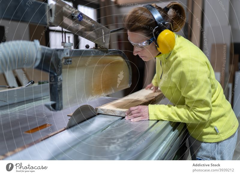 Serious craftswoman working on saw bench machine wood artisan workbench focus joinery workshop occupation wooden board female adult sharp professional job