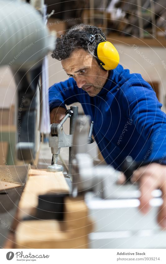 Professional joiner sawing wooden board in workshop man machine job carpenter joinery woodwork workbench concentrate occupation small business male middle age