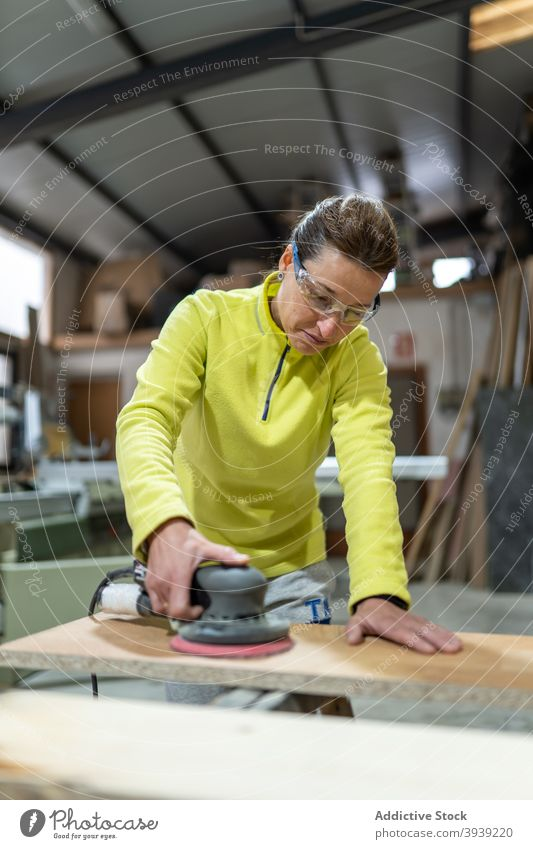 Concentrated woman smoothing wood with sanding machine polish wooden plank sander joinery professional master carpenter skill orbital tool job work female