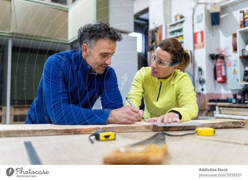 Focused colleagues measuring wood in modern workshop measure woodwork together concentrate master joinery occupation professional coworker man woman adult