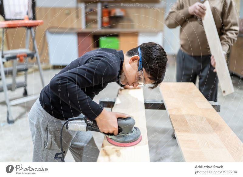 Focused child polishing wood in workshop with unrecognizable grandfather boy sander machine help grandson orbital joiner craftsman occupation wooden panel