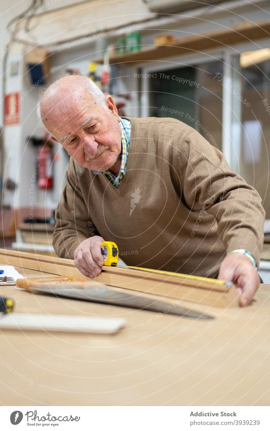 Senior craftsman preparing wood for sawing measure tape woodworker workshop machine workbench joinery occupation male elderly casual material carpenter tool