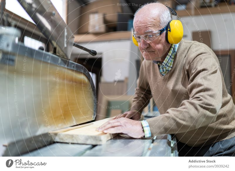 Serious craftsman working on saw bench machine wood artisan workbench focus joinery workshop occupation wooden board professional job manufacture skill