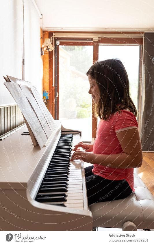 Smiling child playing piano in cozy room in daylight rehearsal read music note musician home instrument positive melody girl kid casual learn adorable acoustic