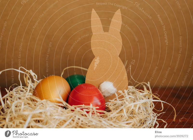 Easter nest with colorful Easter eggs and a handmade Easter bunny Easter Bunny variegated Home-made Nest Easter egg nest Brown rabbit colored