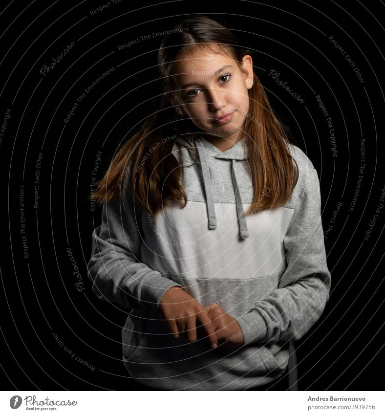 Beautiful little girl in a gray sweatshirt and with two pigtails looking up with funny attitude on a black background daughter joy positive cute people face