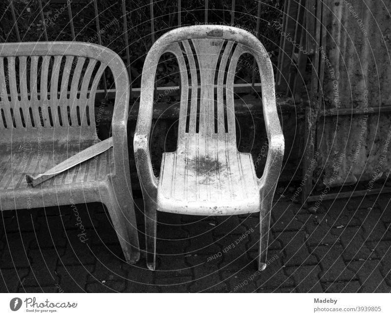 Dirty old garden furniture made of white plastic at the bulky waste on the sidewalk Chair Bench Camping Outdoor furniture camping furniture Sit Lounge suite