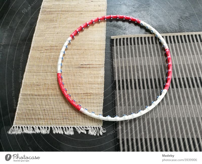 Hula hoops in red and white on two plain modern carpets made of natural fibre on the grey concrete floor of a designer apartment hula hoop Tire Fitness Sports