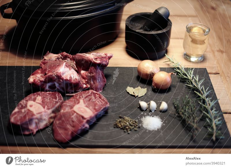 Beinscheiben vom Rind, Knochen vom Rind, Salz, Pfeffer, Knoblauch, Wein im Glas, Thymian, Rosmarin, Lorbeerblätter, und Knoblauch auf einem dunklen Brett vor einem Mörser und einem Bräter auf einem Holztisch
