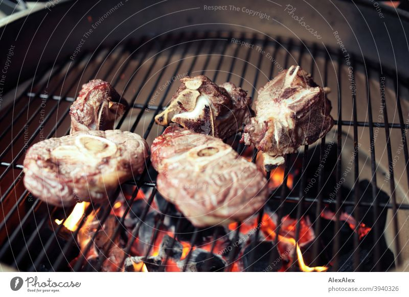 Several leg slices and beef bones ready grilled on a kamado grill on the grill grate Grill Ceramic grill Kamado Green Hot Soot Rust Pottery blazing BBQ