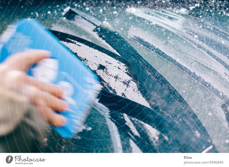 Hand scrapes the icy car window free in winter with an ice scraper Car window Frost Ice Winter Free Scratch Slice Frozen iced Car Window Windscreen Blue Cold