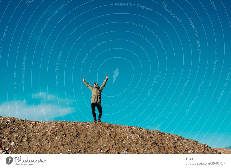 A man stands on a gravel hill against a blue sky and joyfully stretches his arms in the air Joy Freedom Blue sky Arms in the air pleased Good mood Hill Sky