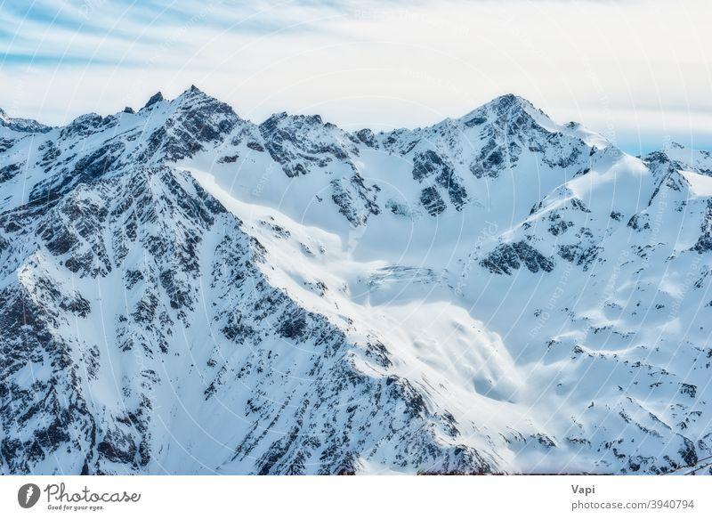 Snowy blue mountains in clouds winter sky snow white caucasus alps elbrus ice nature high peak landscape glacier cold beautiful alpine ski sun travel resort top