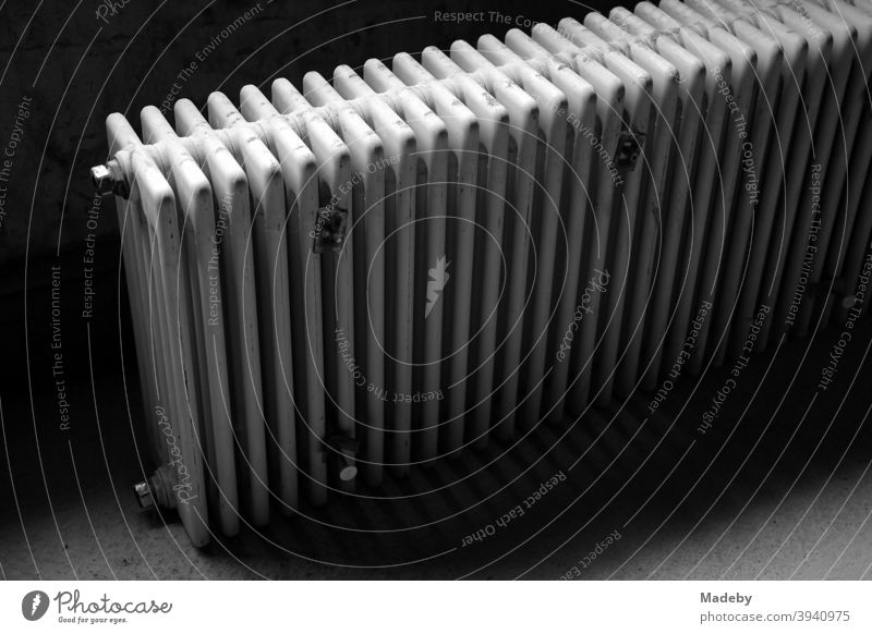 Discarded old radiator in the dark cellar of an old country house in Bavaria, photographed in classic black and white Heating Heater Warmth Old discarded Energy
