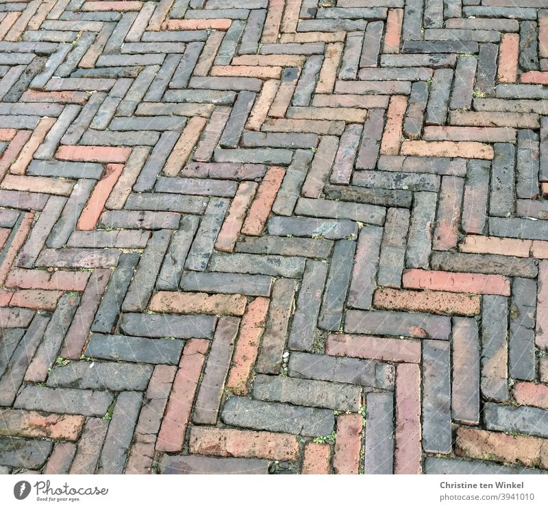 Old and worn grey and reddish paving stones / slips are laid in a herringbone or spike pattern Paving stone stone pavement straps Floor covering Pavement