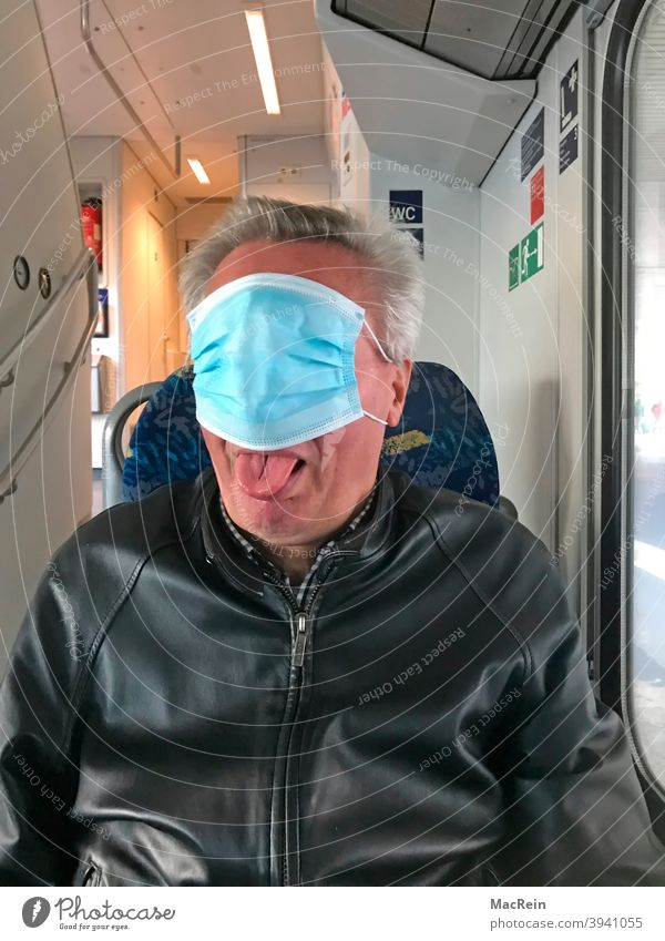Man with mouth and nose protection covers his face in a public transport vehicle 65-75 years covid 19 corona Colour photo Ignorant Interior shot