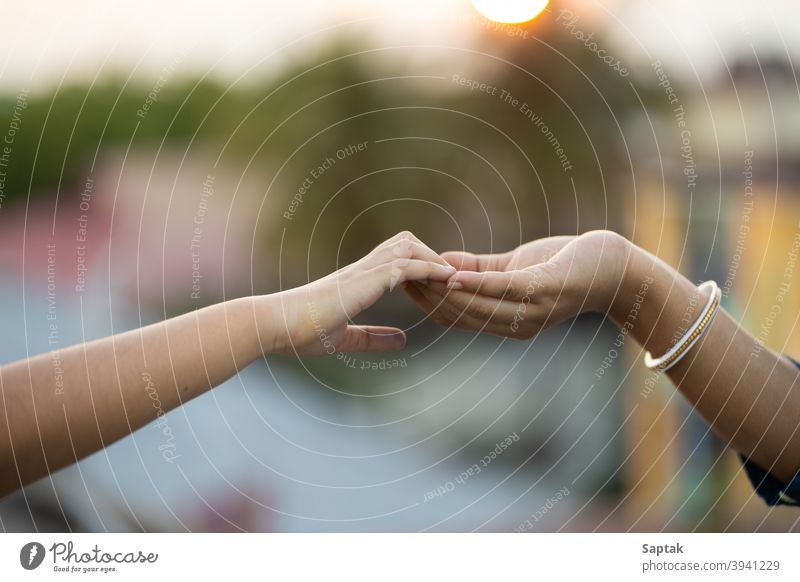 Woman and child holding hands outdoors at sunset bonding togetherness calm mother daughter help assistance giving hope trust love peace finger symbolic family