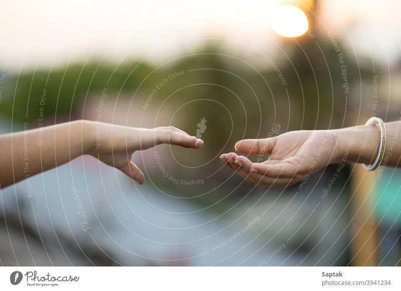 Child and woman reaching out to hold hands during sunset bonding togetherness calm mother daughter help assistance giving hope trust love peace finger symbolic