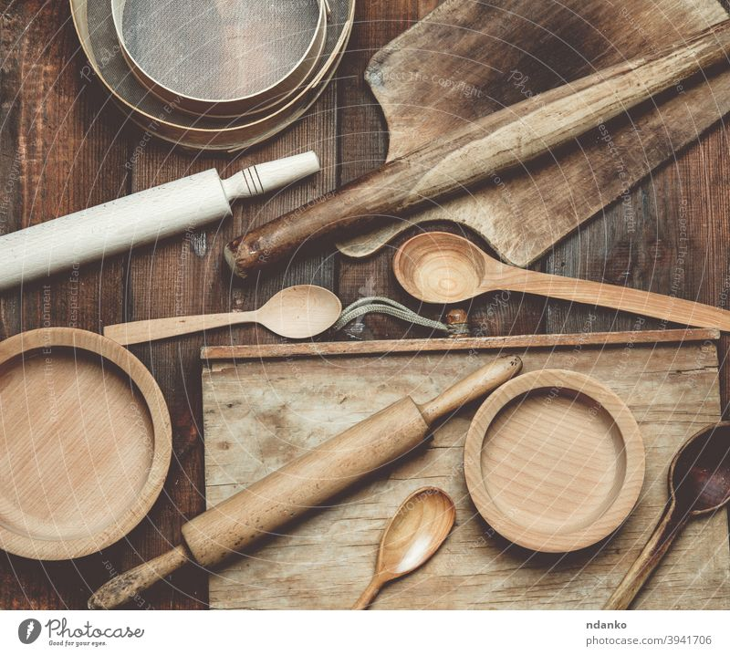 wooden kitchen vintage items: sieve, rolling pin, empty spoons and round plates on brown wooden table menu above backdrop background board cooking cuisine