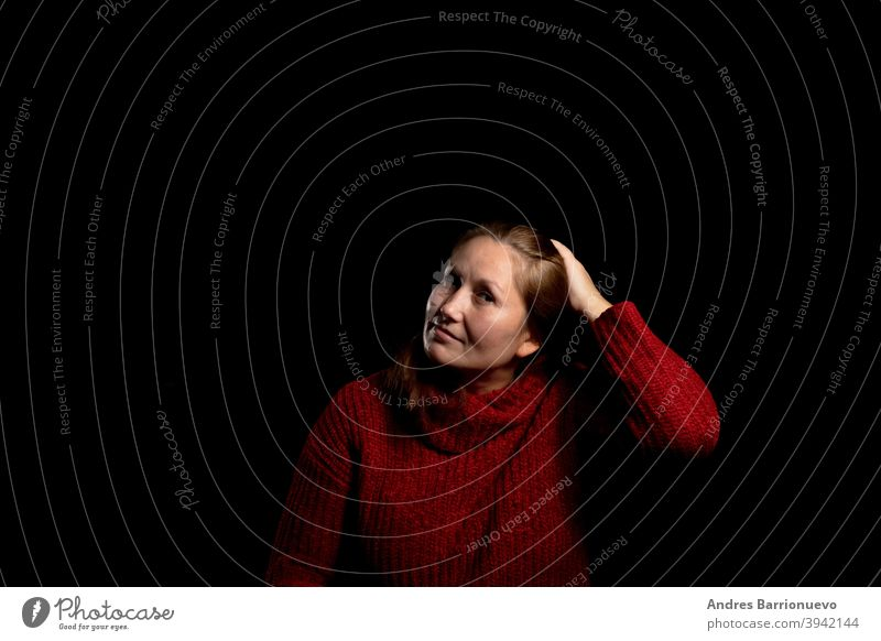 Pretty woman in a red woolen sweater posing smiling on black studio background. Copy space cute one girl agreement gesture happy casual closeup pretty portrait